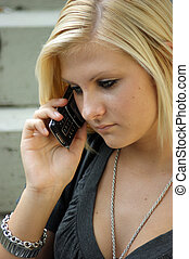 Young, blonde girl with a mobile phone