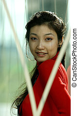 Portrait of a young Asian girl in a red pullover by a...
