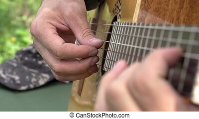 Playing the Guitar - Fingers guitarist slowly pull the...
