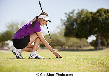 Beautiful woman playing golf - Young beautiful woman placing...
