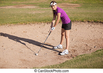 Female golfer on a sand trap - Cute Hispanic female golfer...