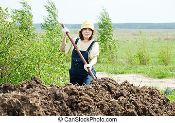 Woman works with  manure