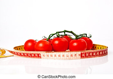 Diet weight loss concept with tape measure organic tomatoes