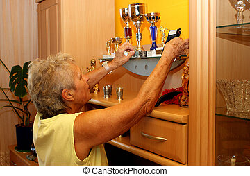 Old woman cleans proud of their trophies and awards