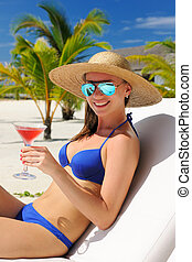 Woman at poolside with cosmopolitan cocktail - Woman in hat...