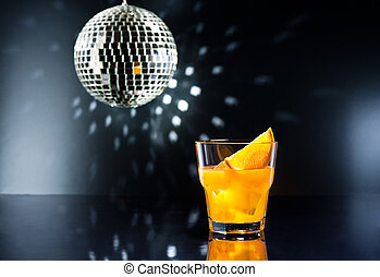 screw driver cocktail in front of disco lights