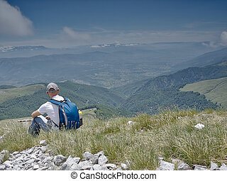 The mountaineer pauses - Man sitting in a meadow in the...