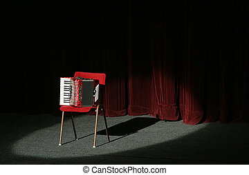 accordion on stage, lighted with a spot light, velvet...