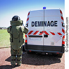Bomb Squad Deminage - Young male soldier in bomb suit behind...