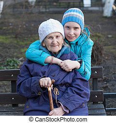 Granddaughter embracing her grandmother on the street