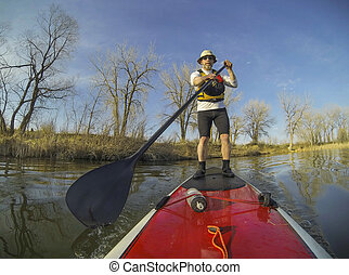 paddling stand up board - mature male paddler on a red stand...