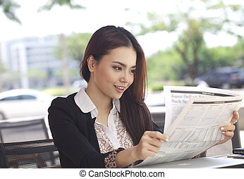 Asian woman read newspaper
