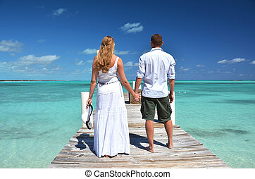 A couple on the wooden jetty Exuma, Bahamas