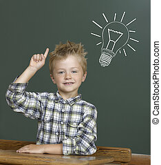 Cheerful smiling child at the blackboard.