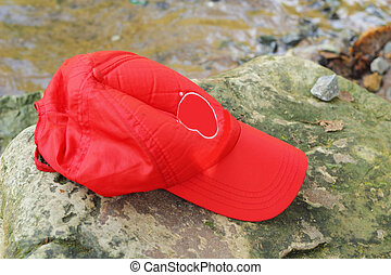 Red cap laying on the rocks on the river.