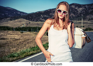 country style - Beautiful young woman posing on a road over...