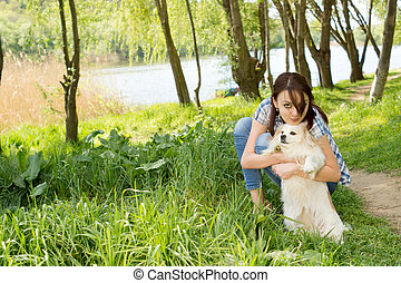 Attractive woman cuddling her tiny dog