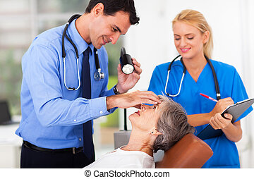 ophthalmologist examining senior womans eye - male...