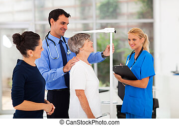 general practitioner measuring senior patient's height in...