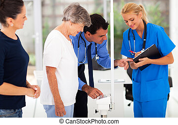 medical doctor monitoring senior patient's weight with his...