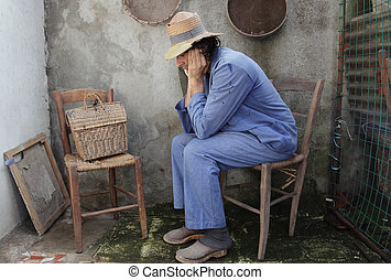 poor farmer at home - pensative poor peasant sititng on a...