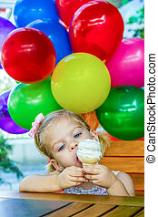 Ice Cream - Little girl eating an ice cream with balloons at...