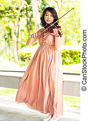 Violinist - Young woman playing violin in garden