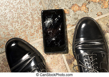 Dropped Smartphone with Cracked Display - A smartphone lies...