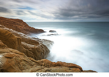 Dark red rocks, foam and waves, sea under bad weather. -...
