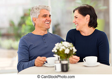 happy middle aged couple enjoying tea - happy laughing...