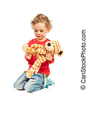 Boy playing with tiger toy - Little blond boy playing with...