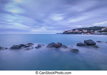 Dark Rocks in a blue ocean on twilight Castiglioncello,...