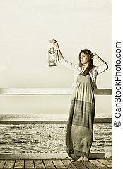 Girl on pier with kerosene lamp - Sepia photo. Full length...