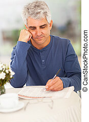 middle aged man going through classified on newspaper -...