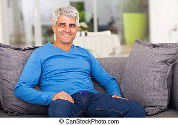 middle aged man relaxing on sofa - cheerful middle aged man...