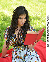 Preety girl reading book outdoors