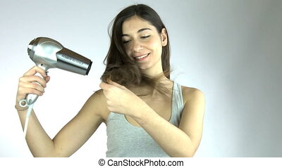 Woman drying her long hair - Young woman with hair dryer and...
