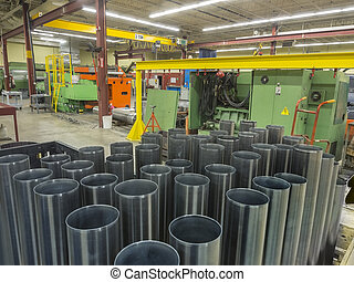 Machine shop floor with milled tubes in foreground