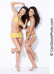 Couple girls having fun with posing against white background