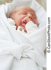 Newborn baby is peacefully sleeping in wrap - selective...
