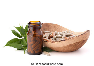 Herbal drug capsules in brown glass bottle isolated on white...