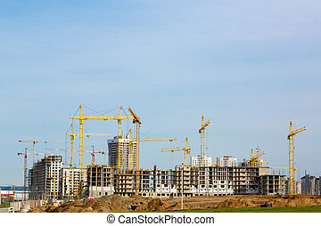Construction site with cranes and buildings under...