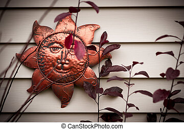 Metal Sun Ornament on Wall - A smiling metal sun face...