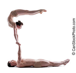 Image of two young acrobats balancing in studio