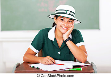 middle school student sitting in classroom - cheerful female...