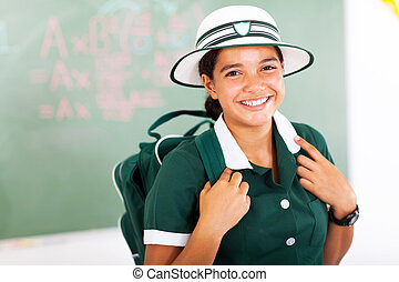 beautiful teenage schoolgirl carrying backpack in classroom