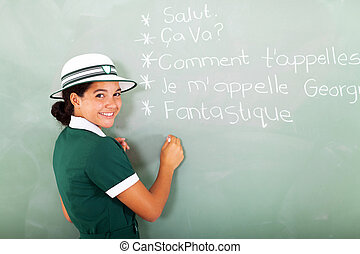 french schoolgirl writing on chalkboard
