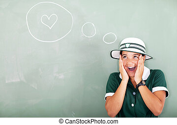 funny schoolgirl thinking about love in classroom