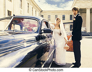 Beautiful happy young bride and groom standing near a retro...