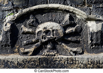 Skull and Crossbones Carving on a Gravestone - A skull and...